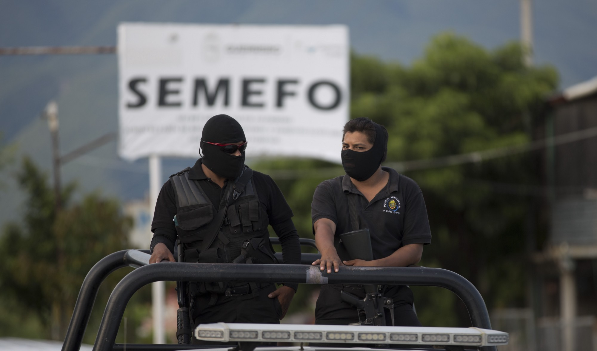 Policías hacen guardia afuera de la morgue en Iguala en el día 5 de octubre de 2014. Mientras tanto, padres de los desaparecidos exigen saber qué sucedió con sus hijos después de que se encontraron fosas clandestinas masivas.