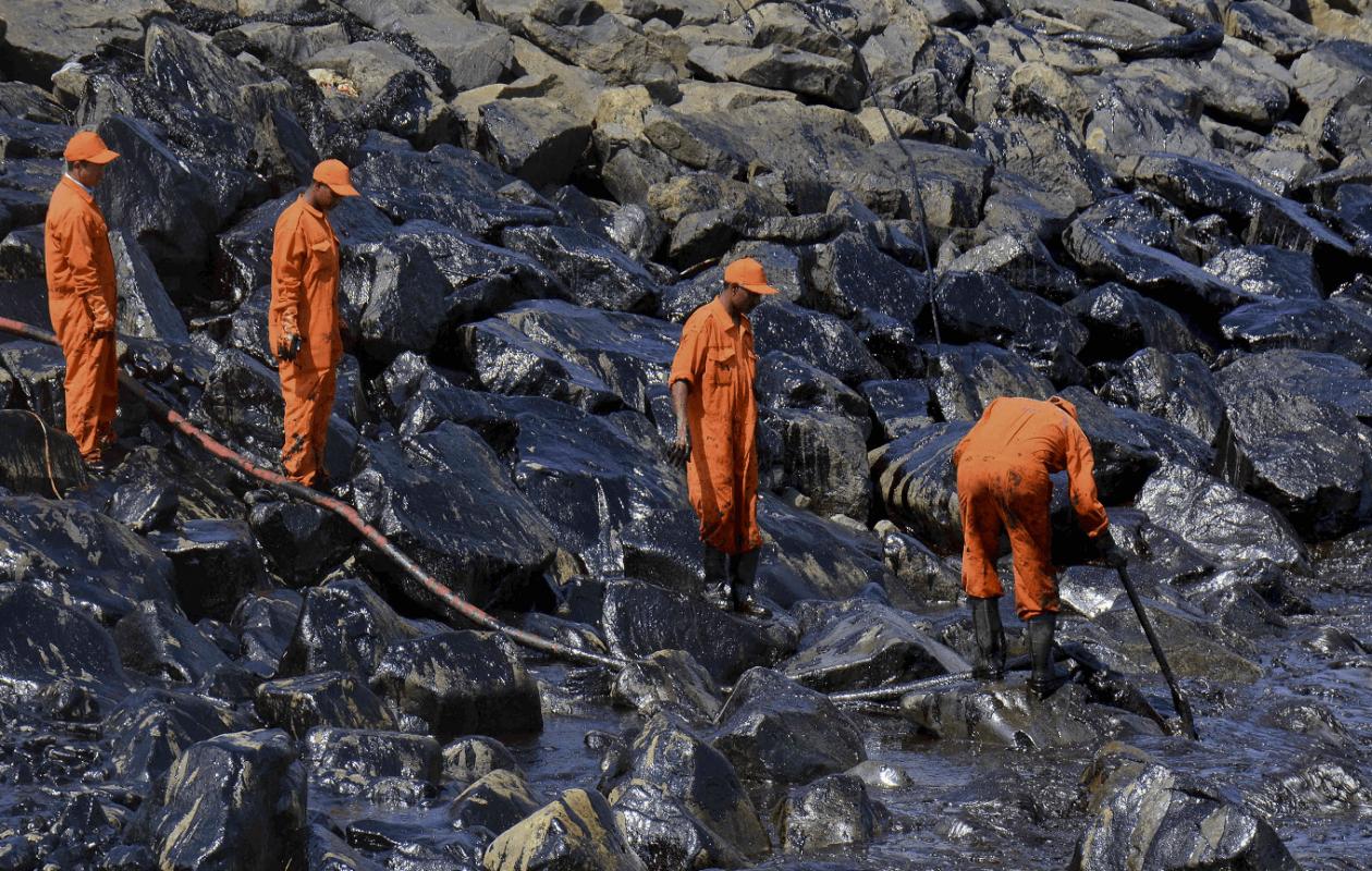Trabajadores indios limpian el petróleo vertido tras choque de dos buques de carga. (AP)