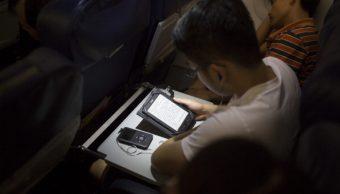 Un pasajero usa una tableta a bordo de un avión. (Getty Images, archivo)