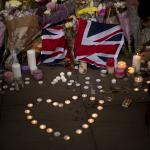 Una bandera británica luce enmedio de flores y velas en honor de las víctimas del atentado en el Manchester Arena