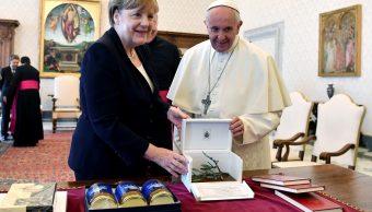 La canciller alemana Angela Merkel intercambia regalos con el papa Francisco durante una reunión en el Vaticano (Reuters)
