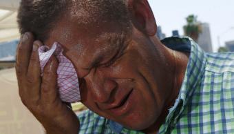 Hombre se limpia la cara ante ola de calor en EU