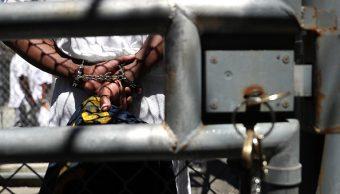 Prisionero camina por pasillos de una carcel