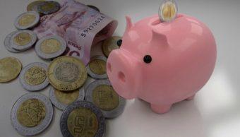 Monedas y billetes mexicanos junto a alcancía. (Noticieros Televisa)