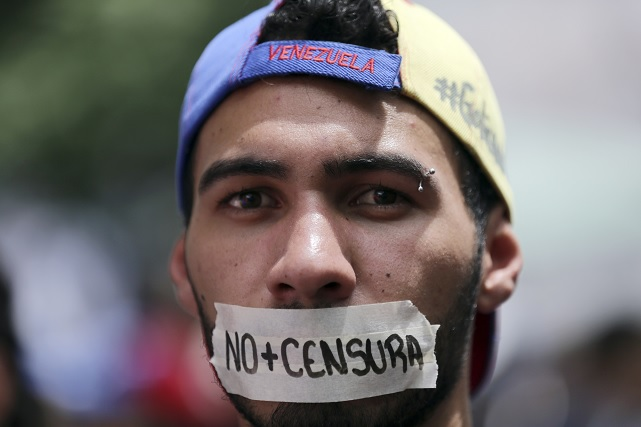 Un hombre lleva un trozo de cinta adhesiva en la boca durante una protesta contra Maduro (AP)