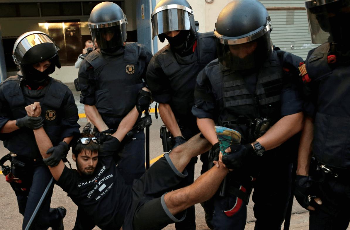 Policías detienen a un joven que protestaba contra los operativos para confiscar material relativo al referendum