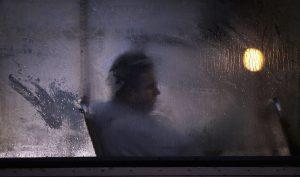 Hombro sombrío tras ventana empañanada