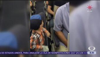 Niño saluda a cada pasajero en el pasillo de un avión