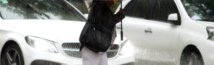 LUna mujer se protege de fuerte lluvia, 7 abril 2019