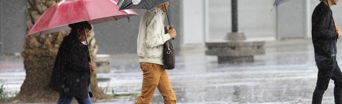 Foto: Algunas personas se protegen de la lluvia, 26 enero 2019
