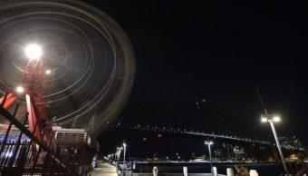 Foto: Las luces del emblemático edificio de la Ópera y del Puente de la Bahía de Sídney se apagaron, 30 marzo 2019