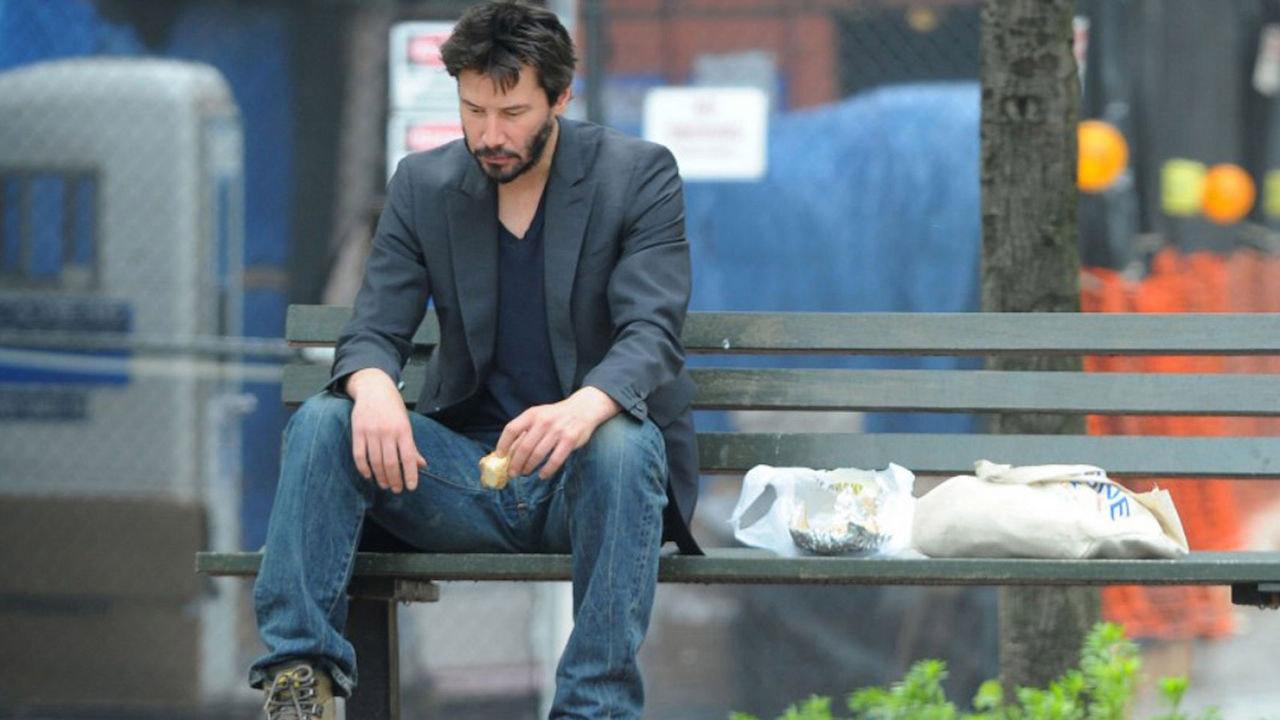 Foto: Keanu Reeves triste sentado en una banca comiendo un sándwich. En 2010