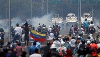 """Foto: Manifestantes se enfrentan a vehículos militares cerca de la base aérea del Generalísimo Francisco de Miranda """"La Carlota"""" en Caracas, Venezuela. El 30 de abril de 2019"""