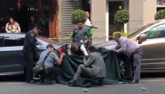 Foto: Policías cubren con una manta el cuerpo de un hombre muerto en Polanco, Ciudad de México. El 13 de mayo de 2019