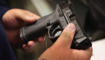 Foto: Una persona observa un arma en una tienda en Illinois, EEUU. El 17 de diciembre de 2012