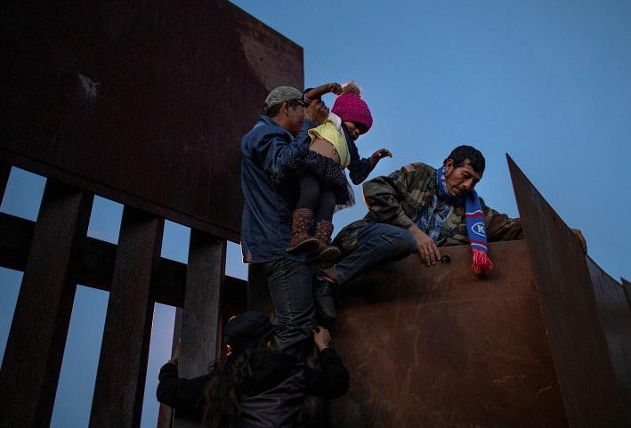 Foto: Un migrante hondureño sostiene a una niña mientras otros saltan el muro fronterizo para ingresar ilegalmente a Estados Unidos desde Tijuana, México. El 2 de diciembre de 218