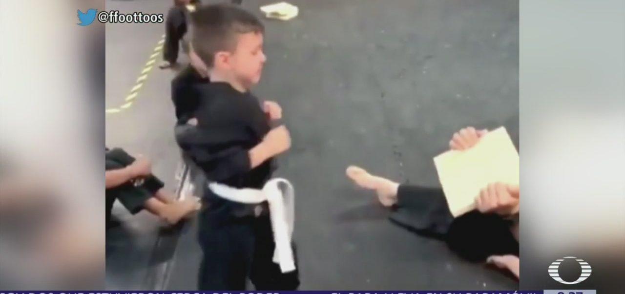 Niños animan a compañero para romper una tabla en karate