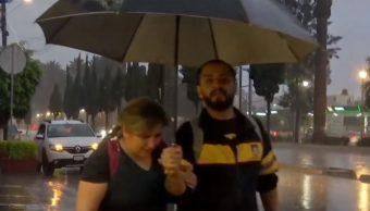 Foto: Dos personas se protegen de la lluvia, 30 junio 2019