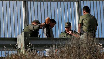 Foto: Agentes fronterizos de Estados Unidos detienen a un migrante al cruzar desde Tijuana, México. El 18 de julio de 2019