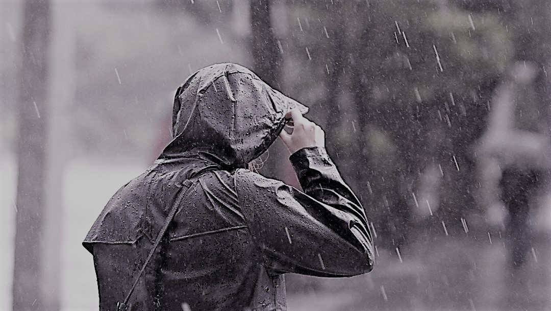FOTO: Una persona se protege de la intensa lluvia que se registra, 20 julio 2019