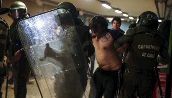 Carabineros de la Policía chilena retienen a un manifestante en la estación del metro en Santiago, Chile, 19 octubre 2019