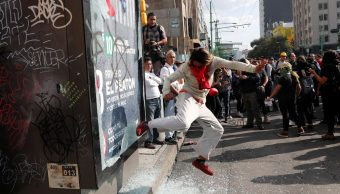 Foto: Un encapuchado patea un local durante la marcha del 2 de octubre. Reuters