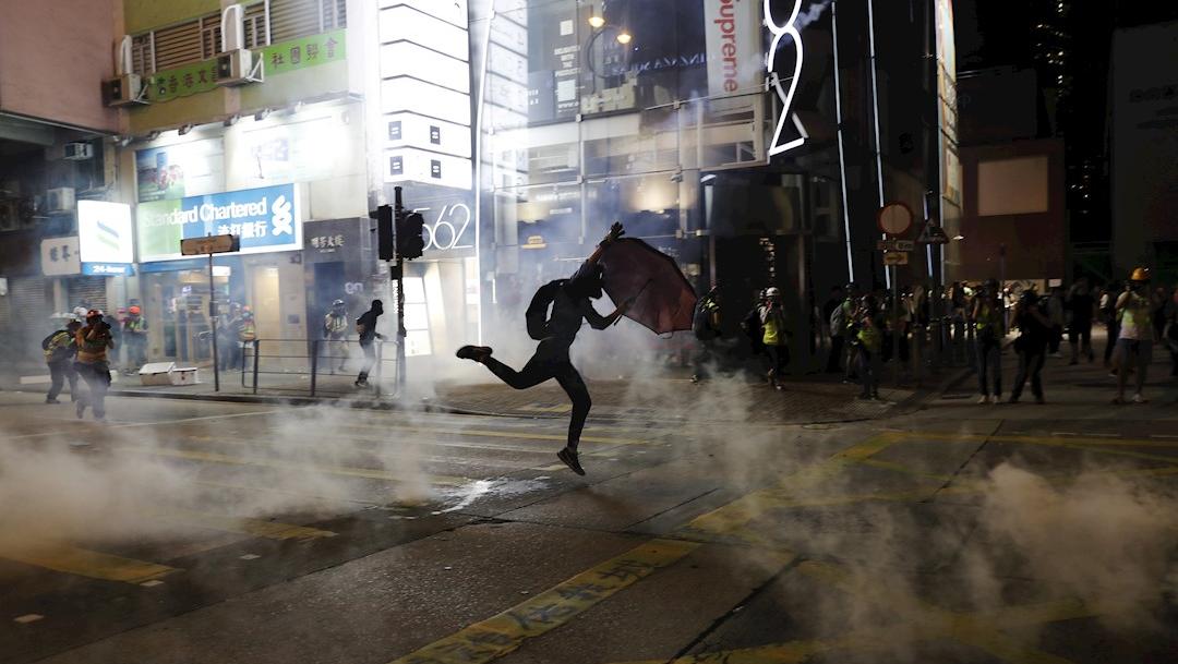 Foto: Un manifestante corre con un paraguas después de que la policía disparó gases lacrimógenos durante la marcha, 20 de octubre de 2019