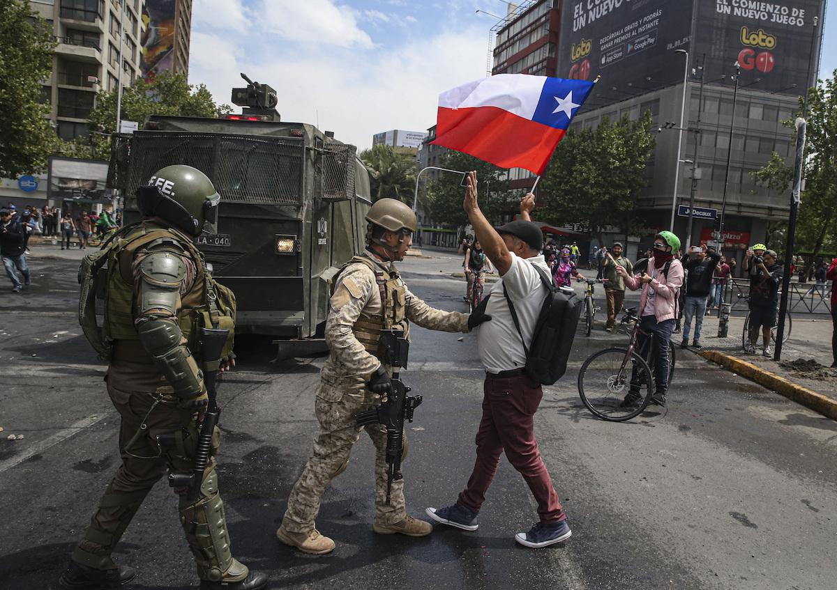 Manifestante enfrentando a soldados en las calles de Santiago de Chile