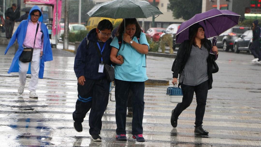 Foto: Una familia se cubren de la lluvia en Ciudad de México. Cuartoscuro/Archivo