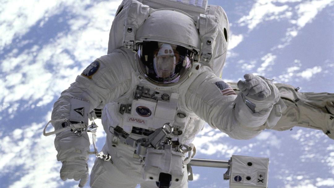 Astronauta-traje-blanco-nasa-mirando-camara-fondo-azul