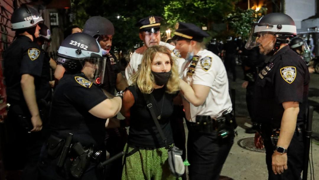 Los oficiales arrestan a una manifestante cerca del Barclay's Center tras las protestas por la muerte de George Floyd. (Foto: AP)