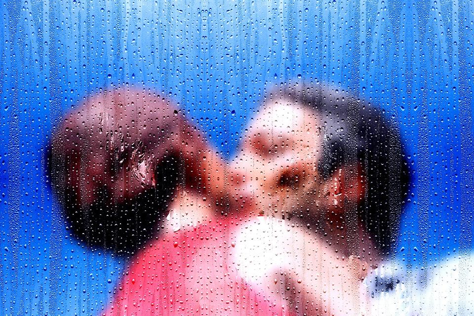 Dos personas se besan bajo la lluvia