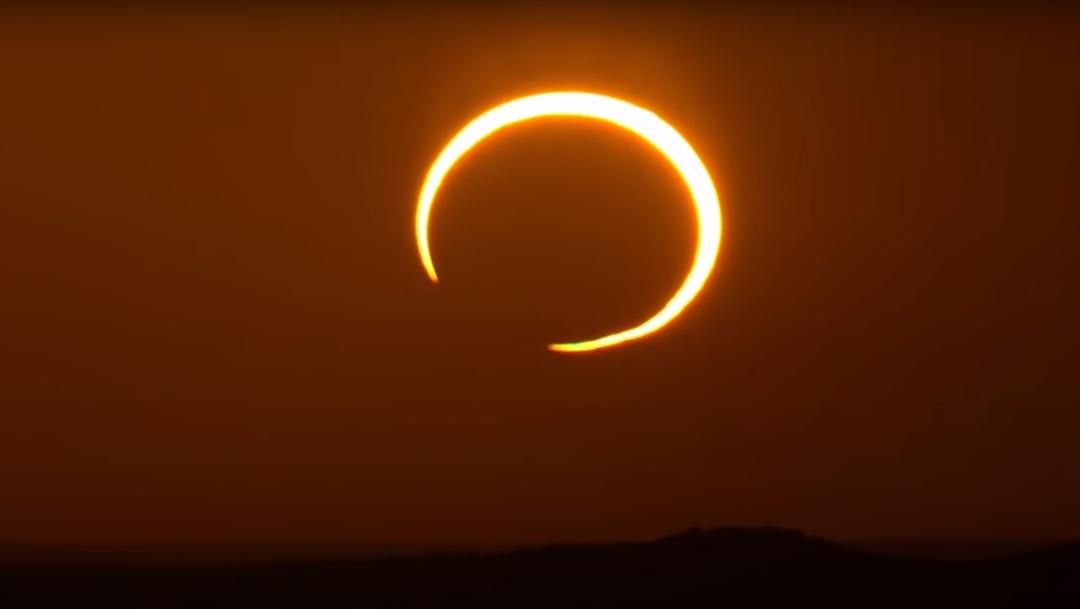 eclipse solar circulo naranja sobre el sol cielo naranja y sombras negras