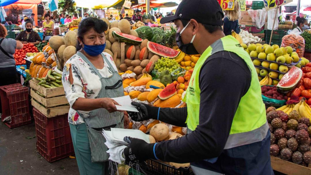hombre entregando cubrebocas a locataria de mercado puesto de frutas