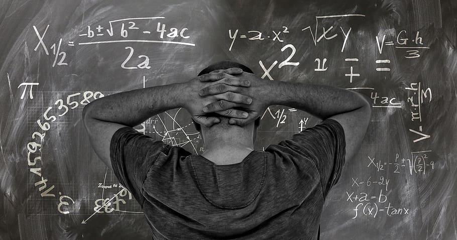 fotografía de hombre frente a problema matemático en un pizarrón