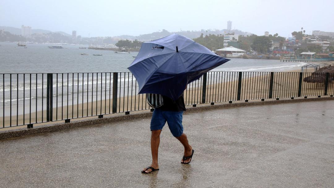 Un joven se resguarda de la lluvia bajo un paraguas frente al mar