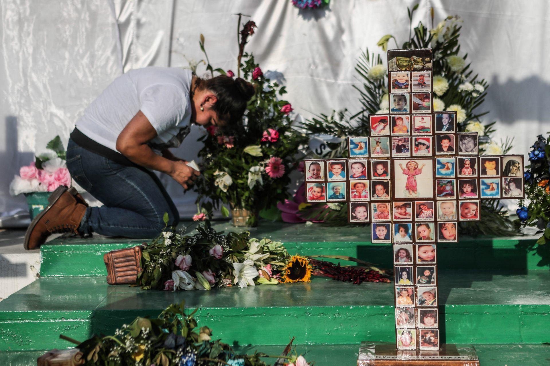 Mujer reza en altar en conmemoración a las víctimas del incendio de la Guardería ABC
