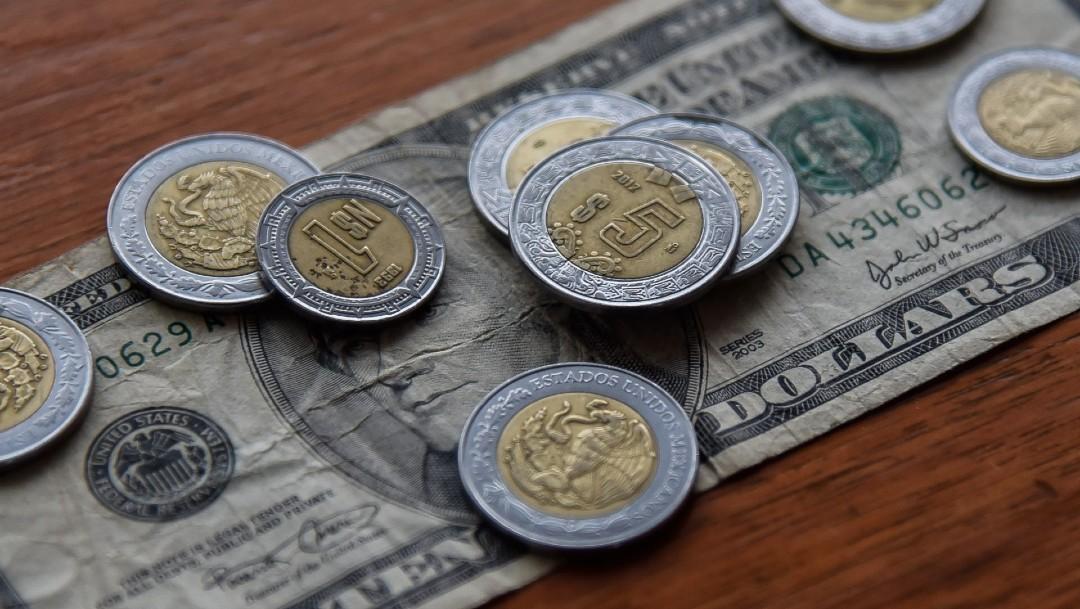 Monedas de pesos mexicanos y dolares en una mesa