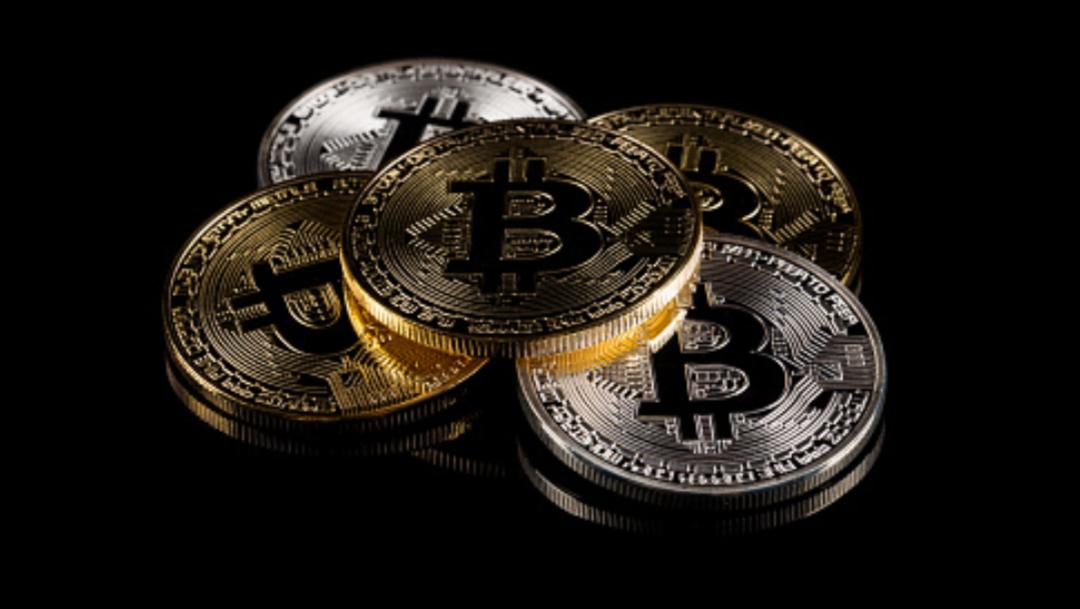 Monedas Bitcoin en un fondo negro getty images