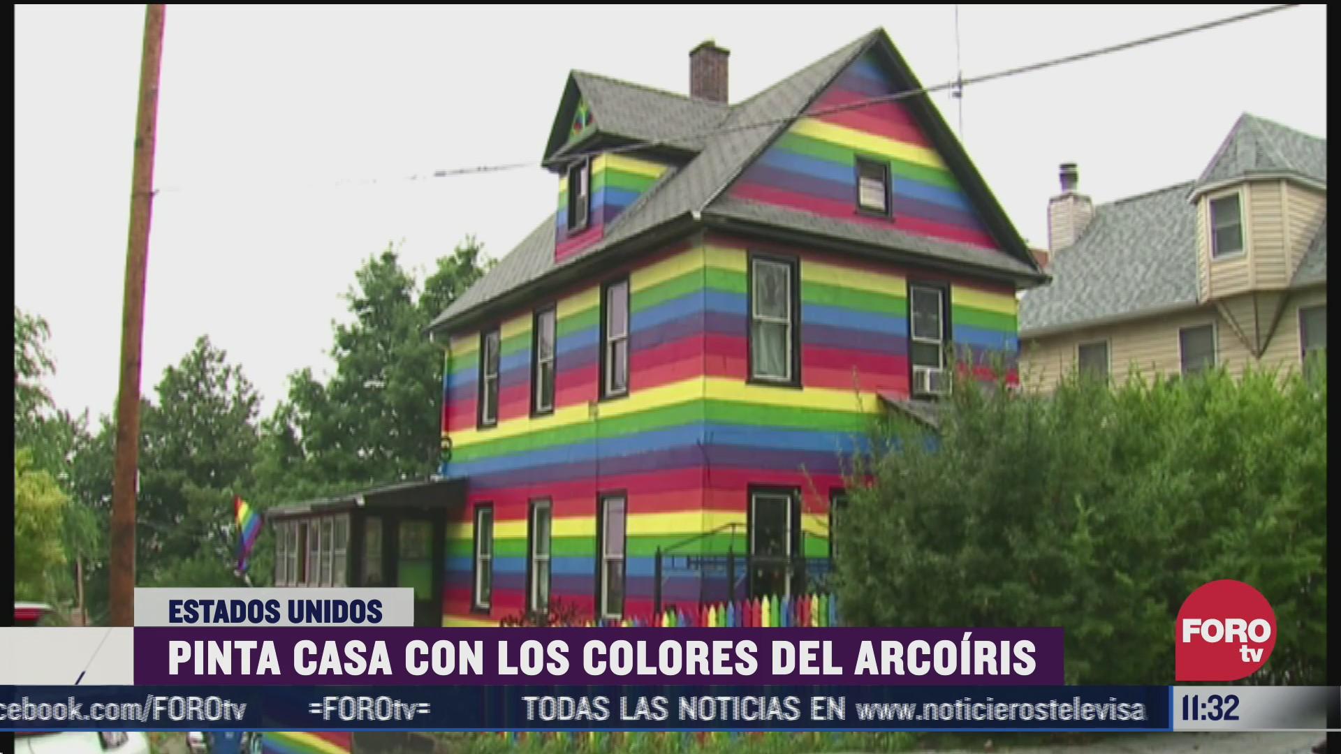 mujer pinta su casa con colores del arcoiris