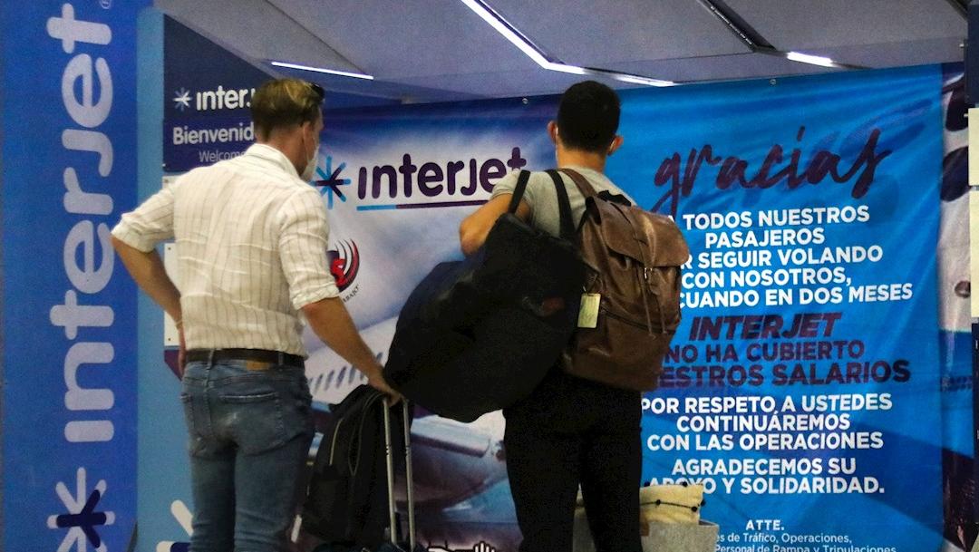 Dos personas observan una pancarta de la aerolínea Interjet en el Aeropuerto Internacional de Ciudad de México