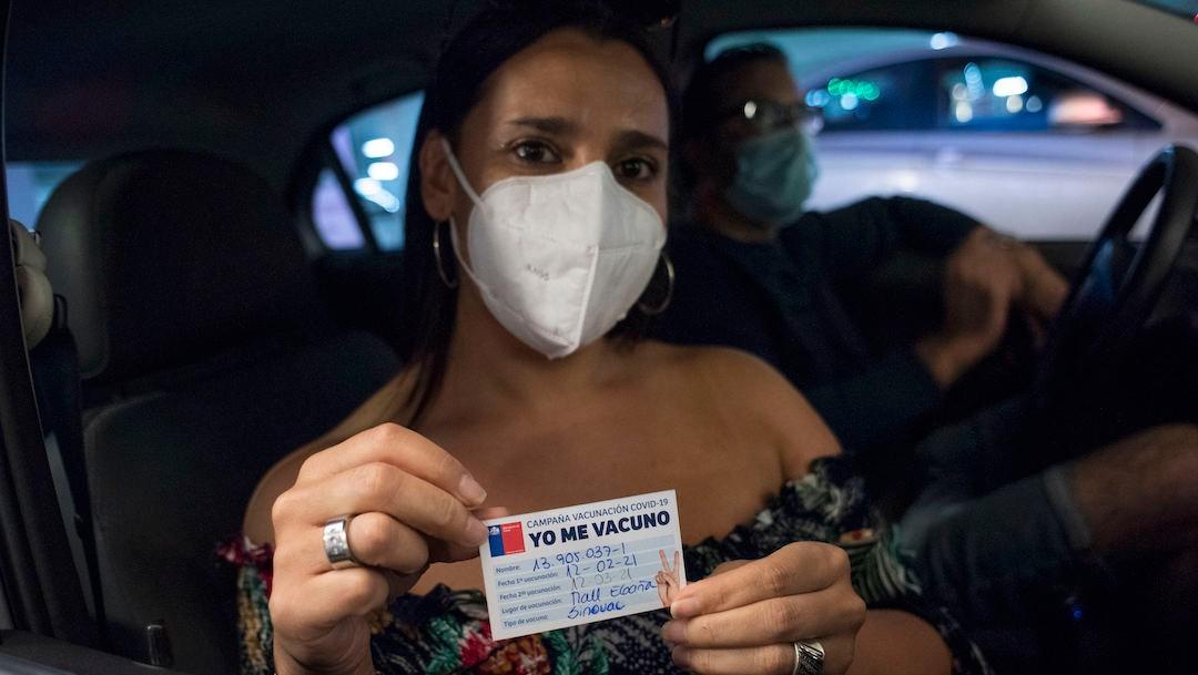 na mujer muestra su cartilla de vacunación contra COVID-19 en Santiago de Chile (Getty Images)