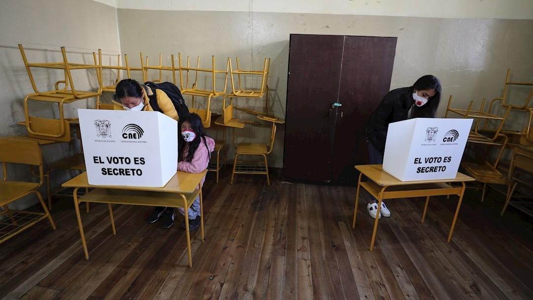 Una niña acompaña a una mujer a votar hoy en un centro electoral en Quito, Ecuador