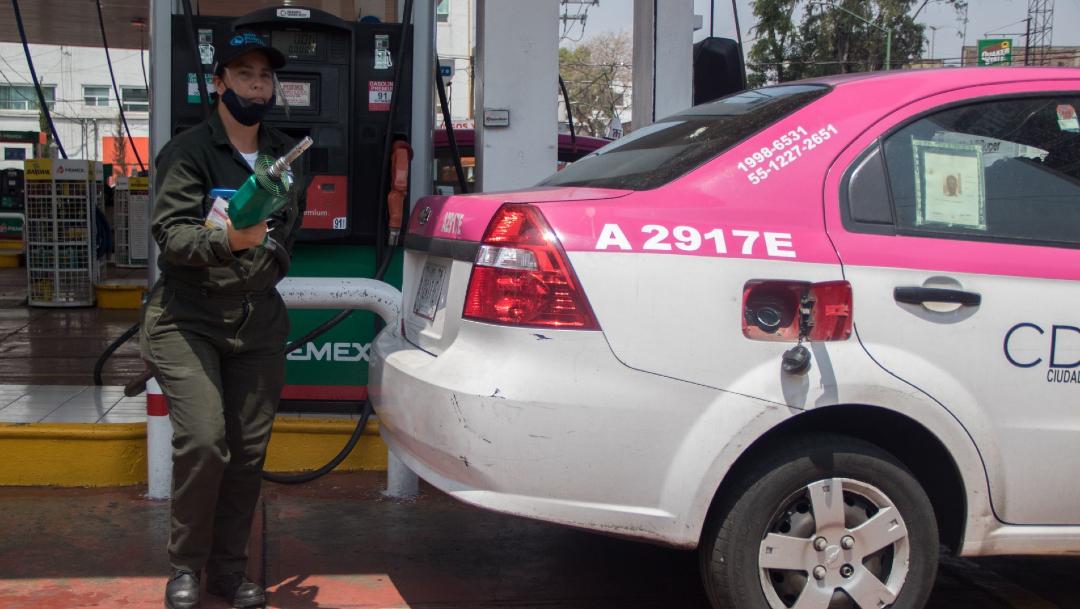 La empleada de una gasolinera atiende a un taxista