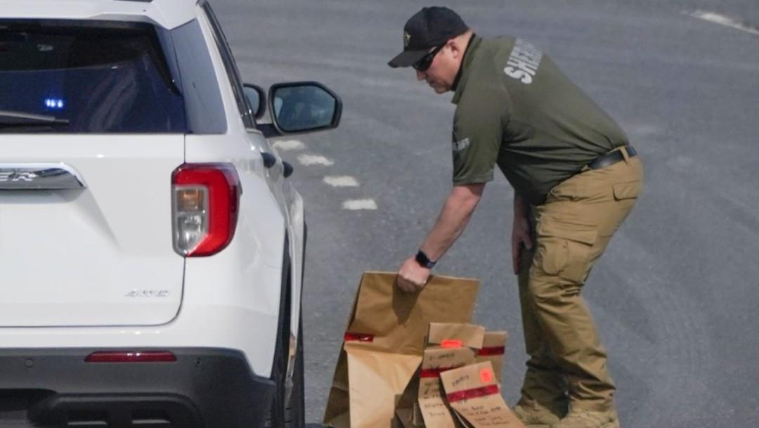 Un ayudante del alguacil del condado de Frederick, Maryland, coloca bolsas de papel con pruebas en un vehículo policial cerca de la escena del tiroteo (AP)