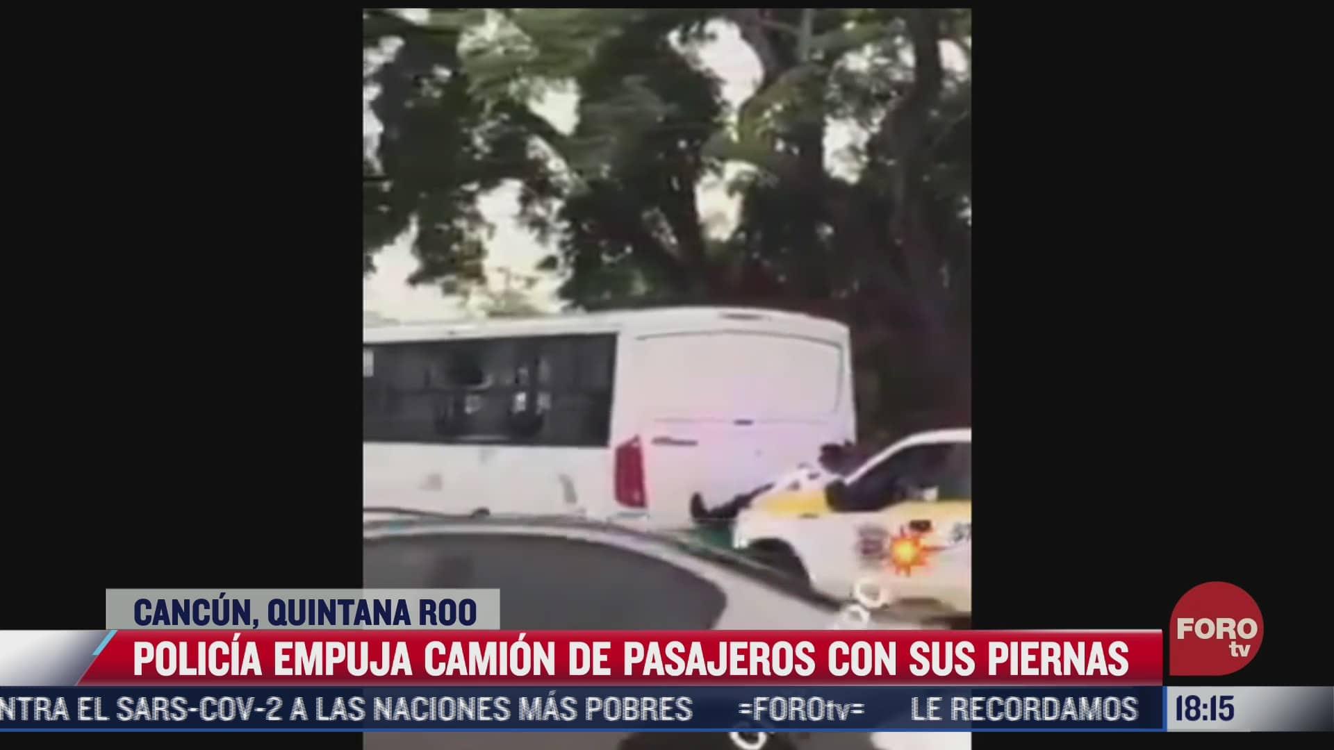 policia empuja con sus piernas camion de pasajeros
