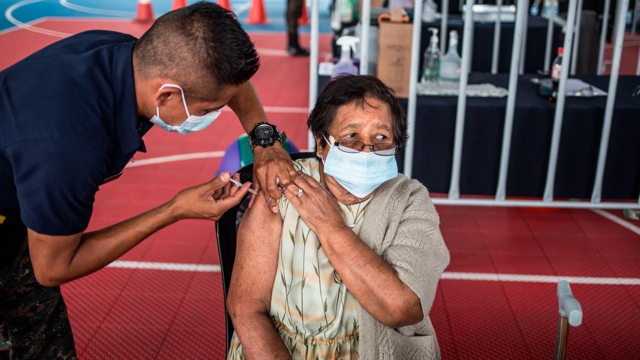 Una mujer adulto mayor recibe la vacuna contra la COVID-19
