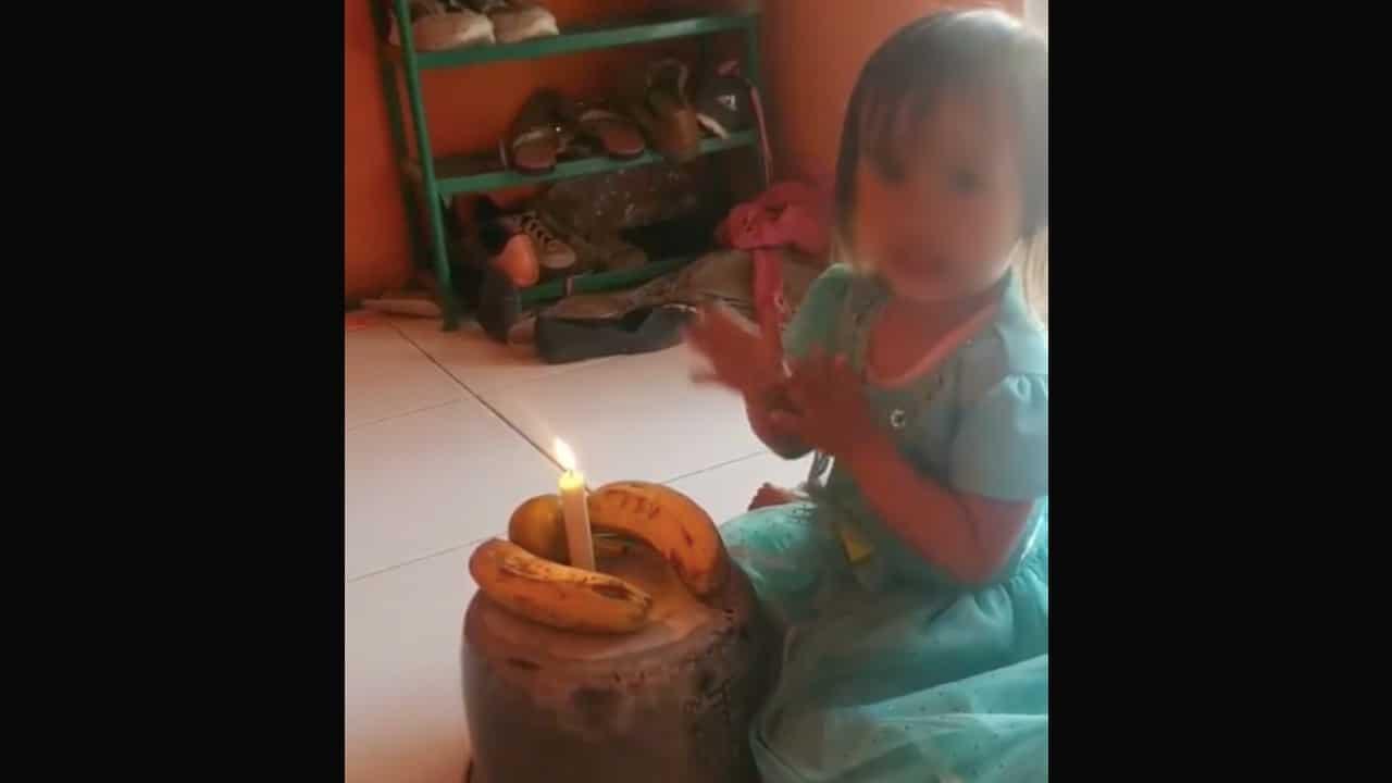 Niña celebra su cumpleaños con pastel formado con dos plátanos