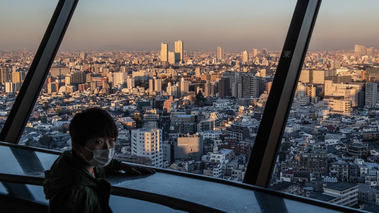 Un joven con cubrebocas mira hacia atrás después de ver el horizonte de Tokio (Getty Images)