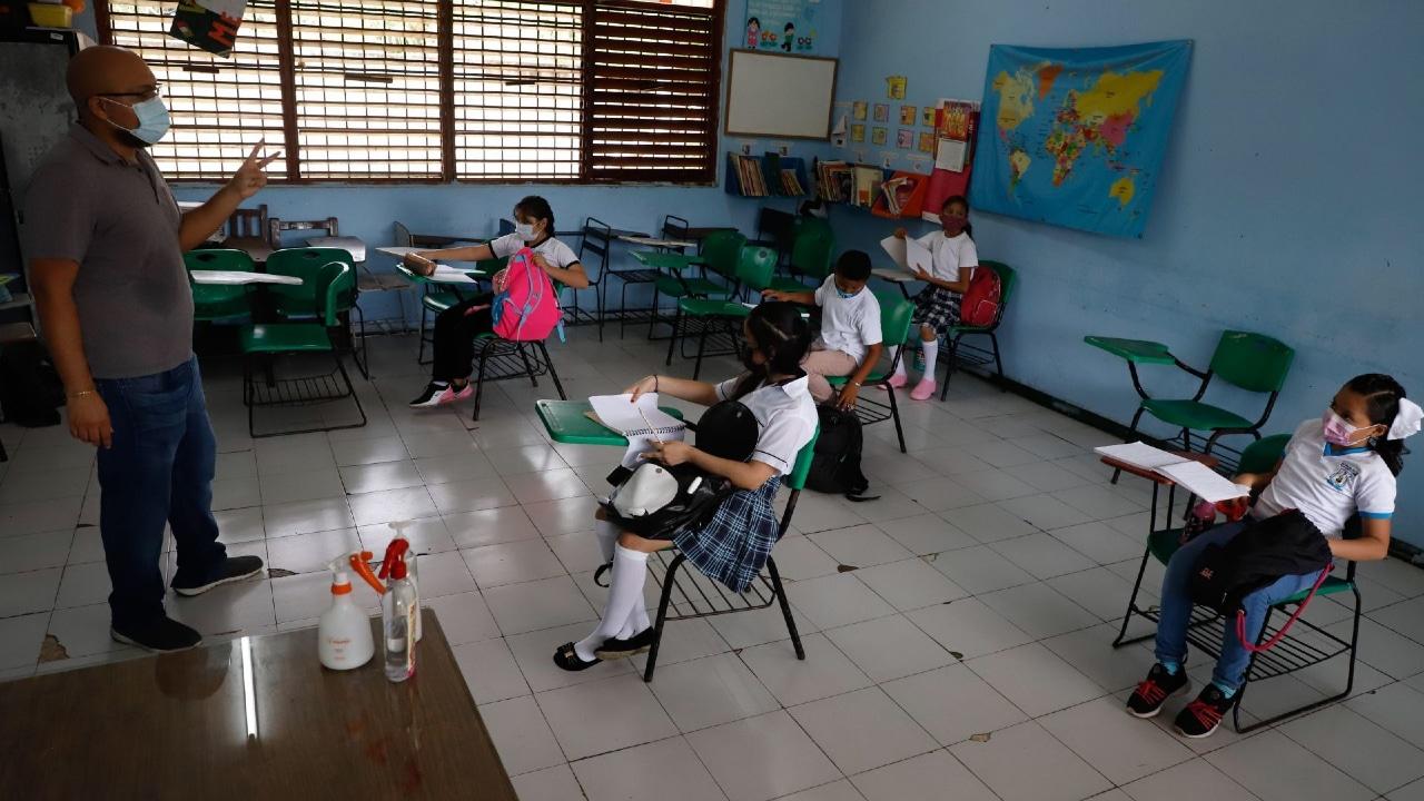 Un grupo pequeño de alumnos toma clases presenciales en su escuela.